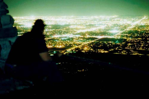 Phoenix Skyline, from South Mountain Park. Camelback mountain visible in top-right of photo. Exposure: approximately 4 minutes at F5.6 using ASA-25 film. A flash was used to light the inside of the building. The figure is anonymous.